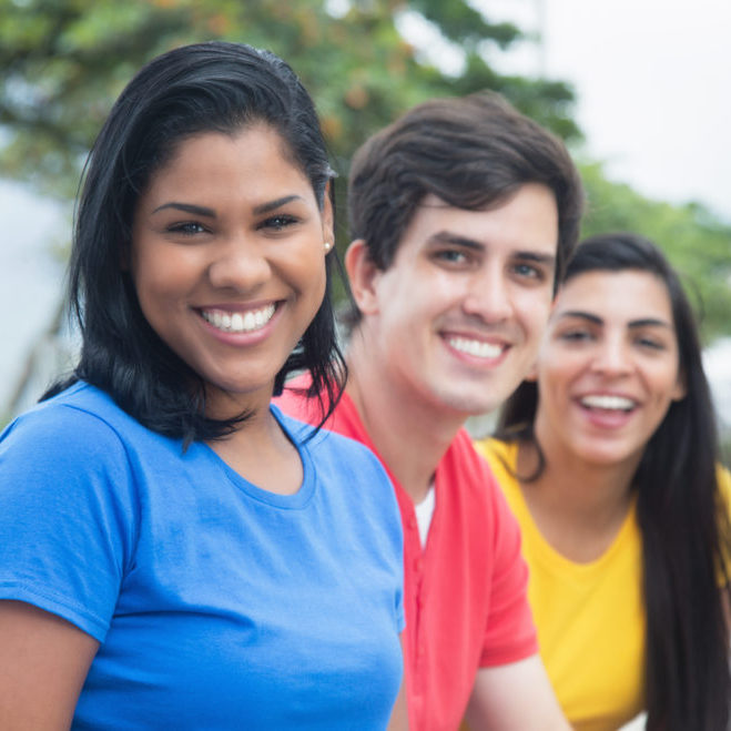 Beautiful latin woman in a blue shirt with caucasian man and native friend outdoor in the city